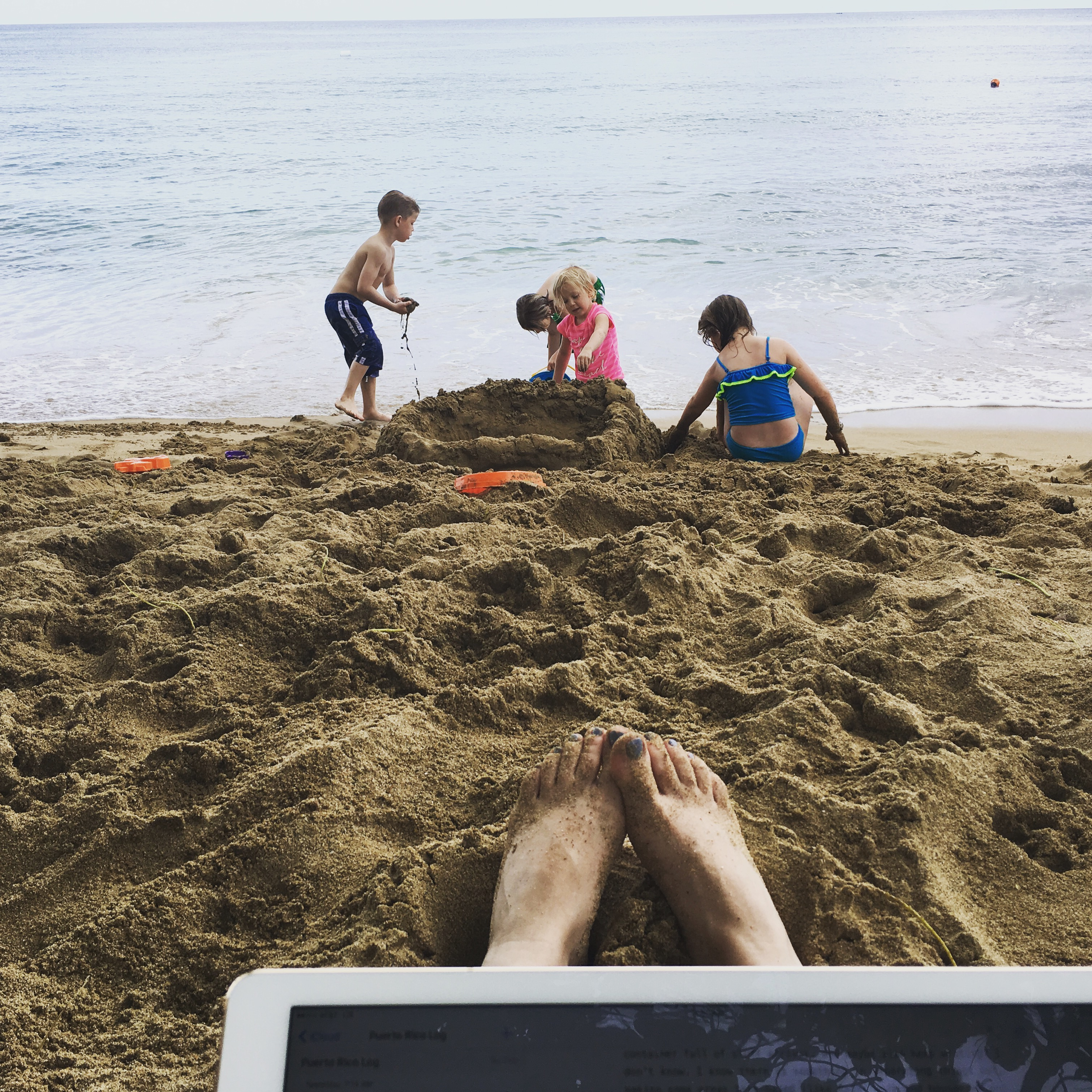 Sitting on the beach working on laptop while kids play.